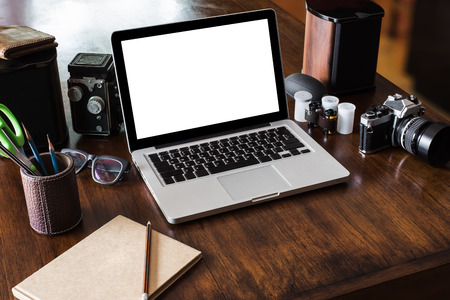 Work space for photographer, designer or hipster style. Have a laptop, film camera, film, speaker, glasses, book, pencil on wooden table.