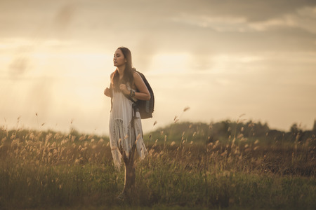 lonely woman: Adventure alone into the meadow at sunset. Stock Photo