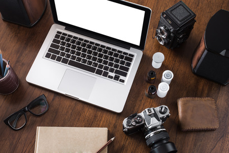 photographers: Work space for photographer, designer or hipster style. Have a laptop, film camera, film, speaker, glasses, book, pencil on wooden table.