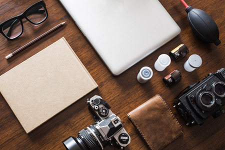 designer: Work space for photographer, designer or hipster style. Have a laptop, film camera, film, speaker, glasses, book, pencil on wooden table.
