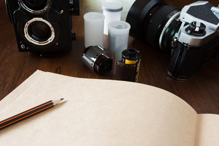 film: Work space for photographer, designer or hipster style. Have a  film camera, film, book, pencil on wooden table.
