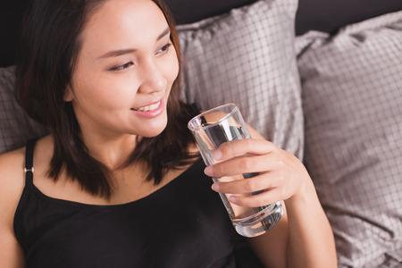 vasos de agua: Mujeres de agua potable en la cama. Su sonriendo.