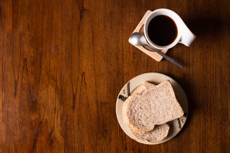 slices of bread: Flat lay of whole wheat bread and and coffee on wooden table.