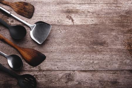 kitchenware: Old kitchenware on wooden background.