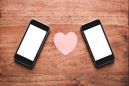 man and woman sex: Two smartphones and hearts paper on wooden table.