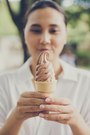 hot temper: Mujer que sostiene el helado. Ella es feliz en el tiempo de vacaciones. Foto de archivo
