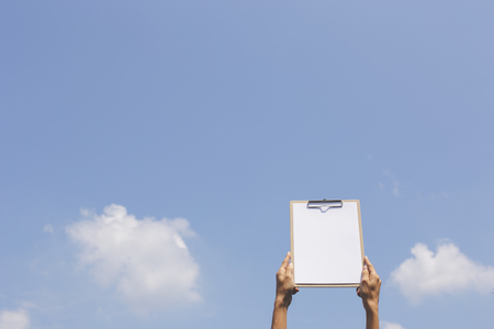 paper board: Hand holding paper board up to the sky. Concept for success or other message.