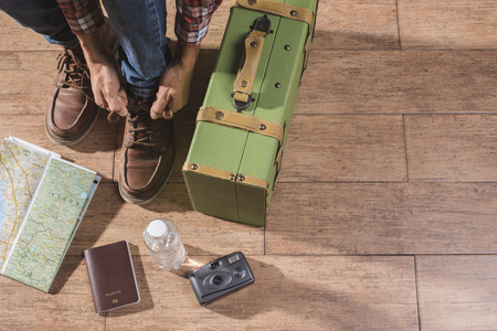 travel luggage: Shoe laces and luggage on wooden floor for travel concept. Stock Photo