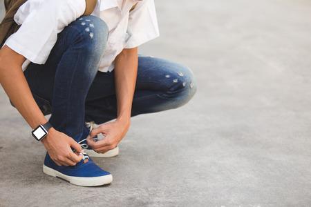 shoe laces: Man shoe laces and wear smart watch.
