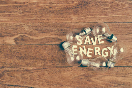 e27: Lots of light bulb and save energy word on wooden background. Concept for save energy.