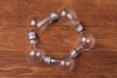 e27: Incandescent lamps on wooden background. Concept for saving energy. Flat lay photography and copy space.