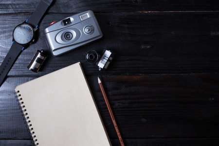 photo story: Book and Film camera on wooden background. Concept for photographer, nostalgia, hipster.