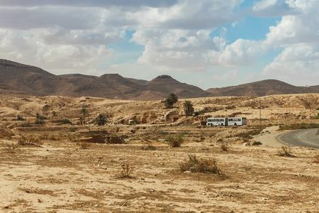 matmata: The bus goes on the road passing through the rocky Sahara desert, Tunisia, Africa. Stock Photo