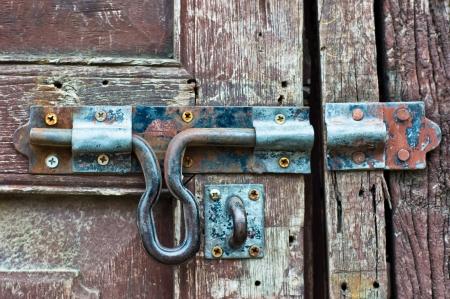door bolt: Cerradura oxidada en la puerta de madera vieja