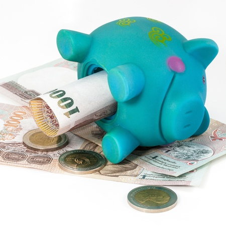 Blue piggy bank laid on bills. photo