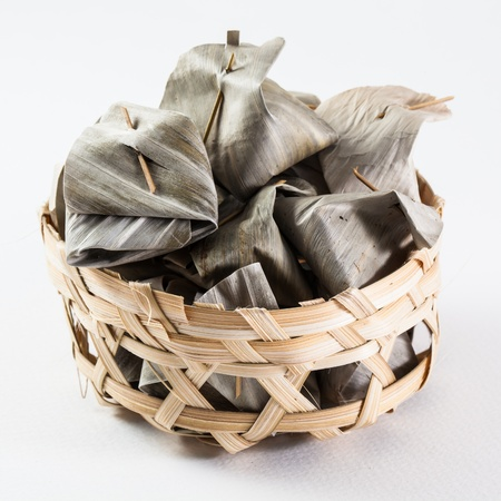 Sweet Thai  traditional dessert cover with banana leaf in bamboo basket photo