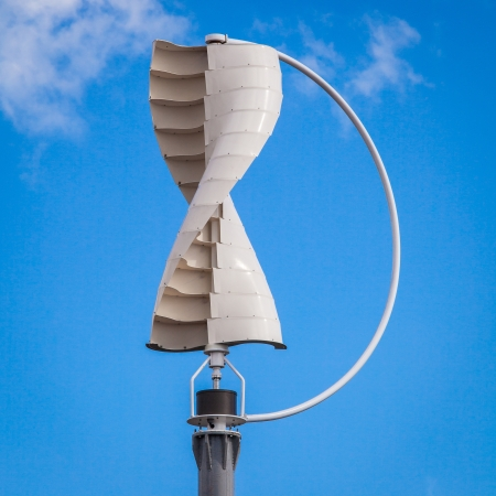 Wind turbine in the vertical shape against blue sky background photo