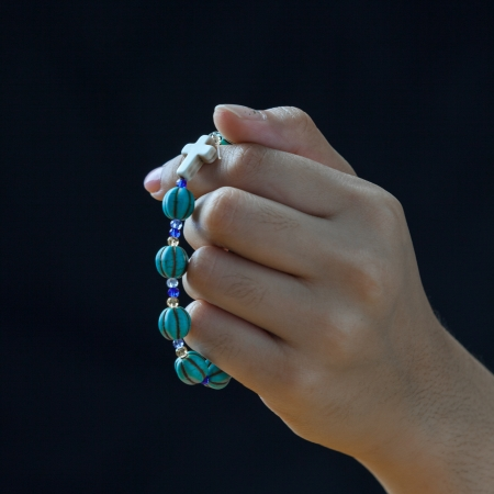Hand holding blue rosary against isolated black background Stock Photo