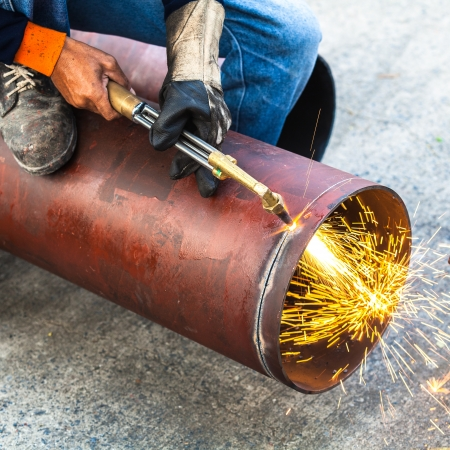 Worker cut big pipe with spark light photo