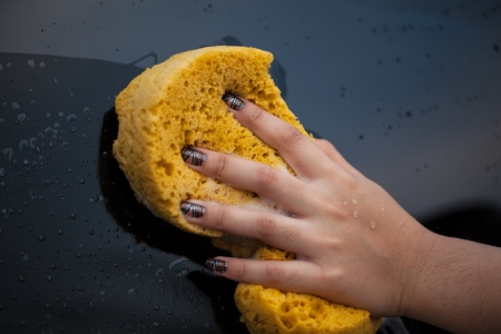 Woman hand washing car with yellow spouge photo