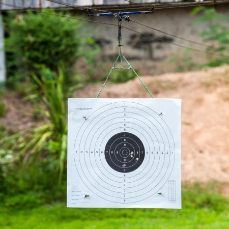 ing: Bull eye target hang ing in shooting range with bullet hole inside