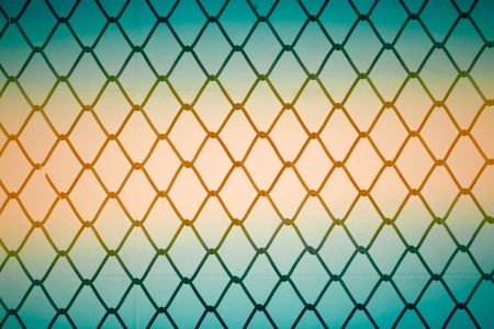Close up of metal twist fence with orange light background Stock Photo - 20927782