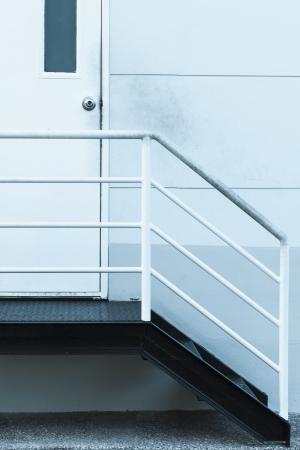 puerta de metal: Escala de acero frente a la puerta de metal blanco