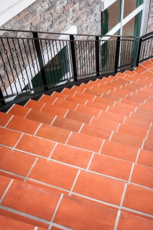 Curve stairs decorated with orange stone pile wiith black iron handrail photo