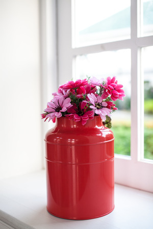 Flowers in watered vase sit on a wooden table in front of windows