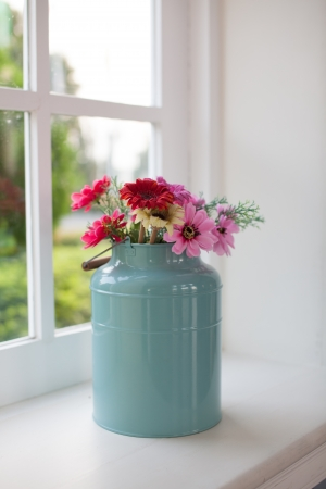 Flowers in watered vase sit on a wooden table in front of windows photo