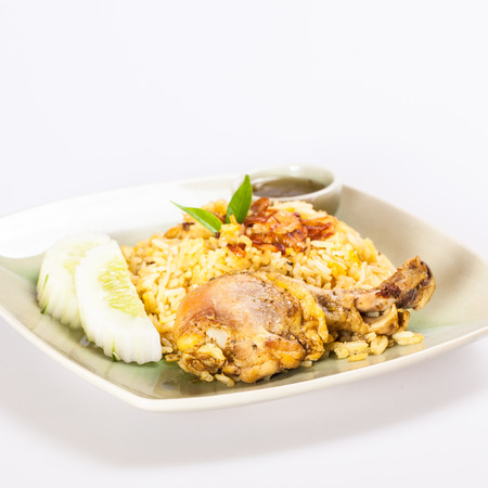 Dish of chicken biryani with sliced cucumbers photo