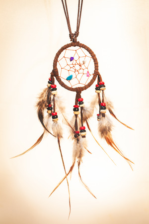 Leather dream catcher on isolated sepia tone background photo