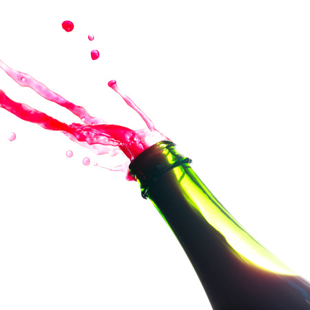 Red wine splash out from green bottle Stock Photo