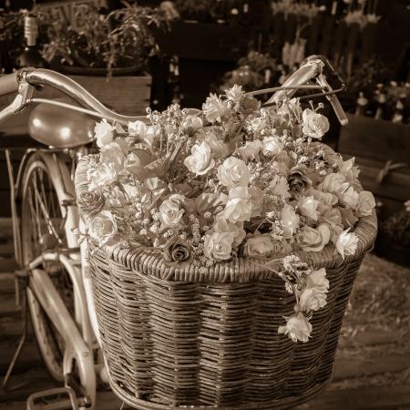 handle bars: Bicicleta de la vendimia con hermosas flores en una cesta en la parte delantera de la moto. Tono sepia
