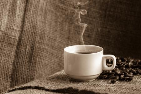 Coffee cup and white smoke on sack cloth. photo