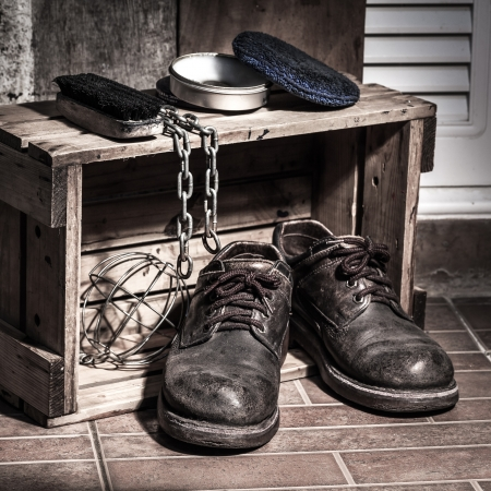 Rugged shoes in wooden box with cleaning set and chain, still light photo