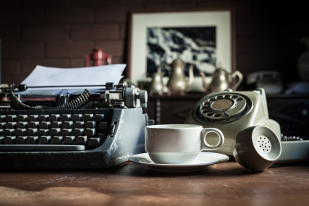 telephone, type writer and flower in silver vase place near old lamp on wooden table