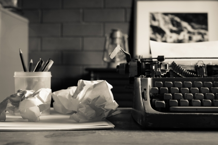 telephone, type writer and flower in silver vase place near old lamp on wooden table photo