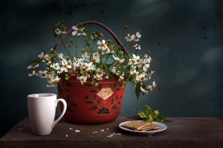 freshment: red basket with white flower, coffee cup and biscuits on wooden table