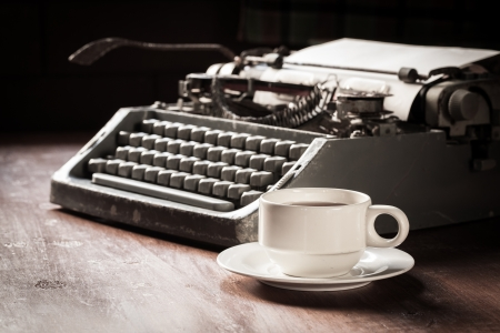 Vintage typewriter and coffee cup on table photo