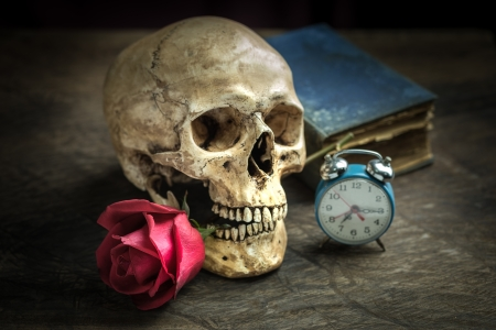 Still life with human skull with red rose in the mouth, old book and alarm clock photo