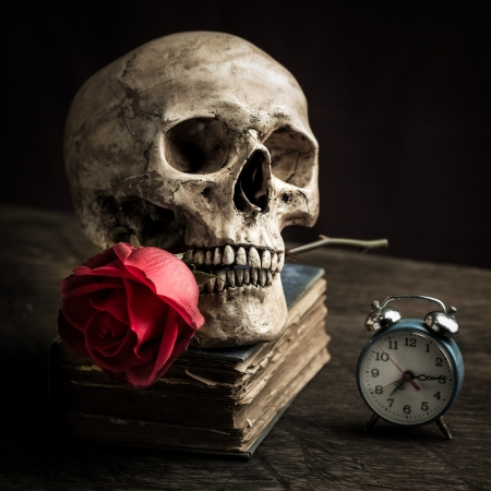 Still life with human skull with red rose in the mouth, old book and alarm clock