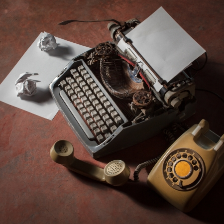 secretarial: Old English type writer with paper sheet and aged telephone, still life Stock Photo