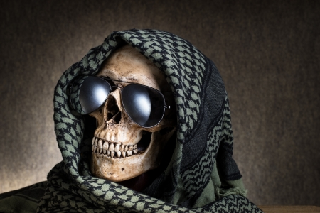 Human skull with shemagh cloth and sun glasses photo