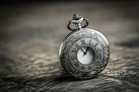 Vintage Antique pocket watch on grunge wooden background photo