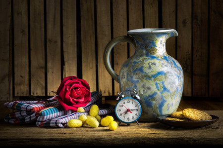 still life with cookies, rose bud, alarm clock, old latern peel of cocoon and silk cloths on the wooden table photo