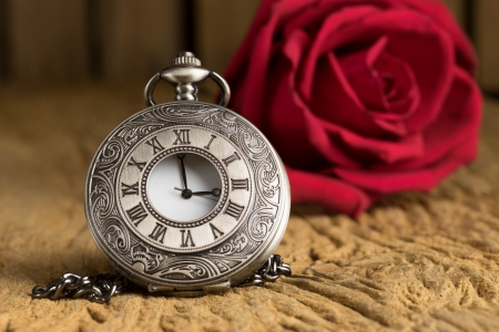 Vintage Antique pocket watch and red rose bud on grunge wooden background photo