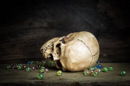 Still life with human skull and crystal ball on wooden table photo