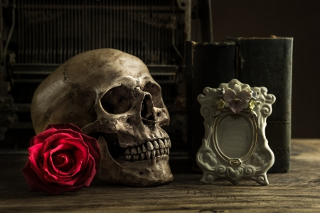 Still life with human skull with red rose, old book and telephone on wooden floor photo