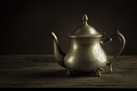 Still life with antique teapot on wooden table Stock Photo
